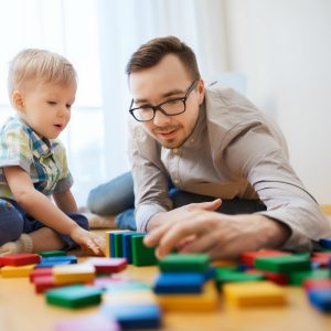 Young father stacking brightly coloured blocks with his son
